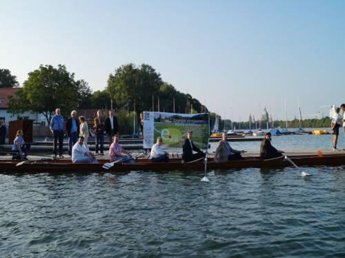 Vereinsmitglieder sitzen gemeinsam mit den Dezernenten in einem Ruderboot