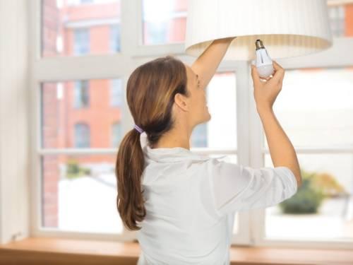 Eine Frau schraubt eine Energiesparlampe in die Fassung ein
