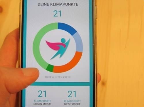 Jemand hält ein Smartphone in der Hand, auf dem die KlimaHelden-App geöffnet ist.