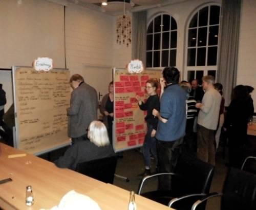 Teilnehmerinnen und Teilnehmer beim Sammeln von Ideen an Moderationswänden.