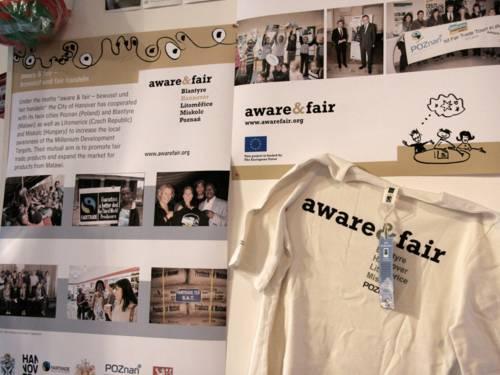 """Ausstellungswand, auf der Fotos und ein T-Shirt mit der Aufschrift """"Aware & Fair"""" zu sehen sind"""
