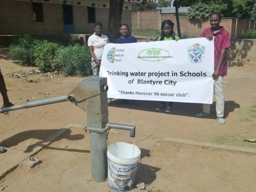 Menschen auf einem Schulgelände mit einem Plakat zum Brunnenprojekt. Im Vordergrund ist die reparierte Wasserpumpe.