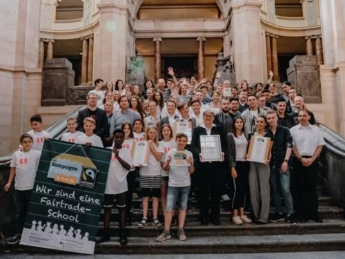 Schülerinnen und Schüler sowie Lehrkräfte der ausgezeichneten Fair Trade Schulen auf der Rathaustreppe; dazwischen die Wirtschafts- und Umweltdezernentin der Landeshauptstadt, Frau Tegtmeyer-Dette.
