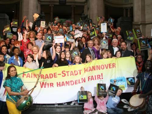 """Gruppenbild mit zahlreichen Aktiven allen Alters auf der Rathaustreppe, die ein Transparent mit der Aufschrift """"Fairtrade-Stadt Hannover - wir handeln fair"""" in den Händen halten."""