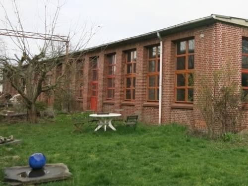 Ein altes Fabrikgebäude mit Rasen und Tischgruppe