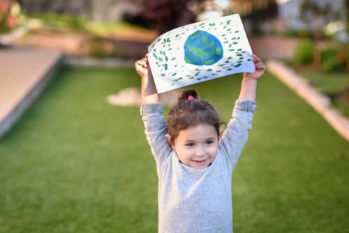 Mädchen, das ein Bild zeigt, auf dem eine gemalte Erde zu sehen ist.