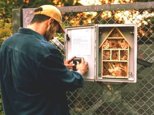Ein Mann steht an einem Geocache, welcher ein Insektenhotel darstellt.