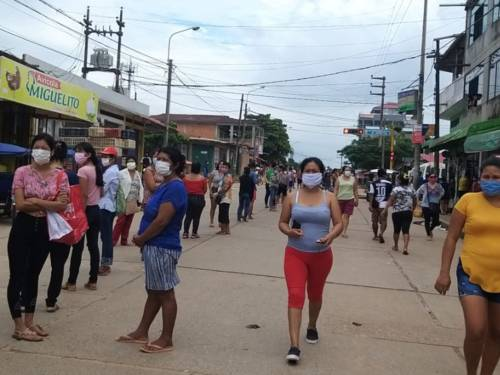 Menschen mit Mundschutz in den Straßen von Yarinacocha in Peru.