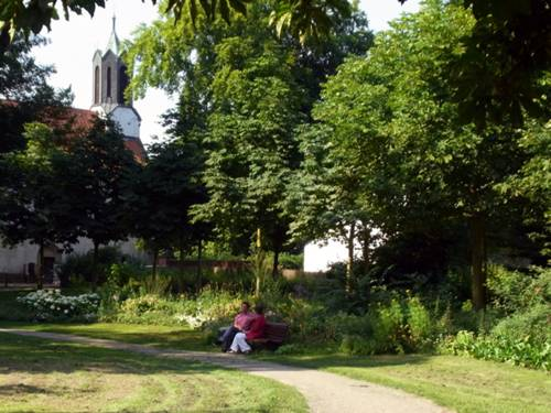 Blick in den Hinüberschen Garten, auf einer Parkbank sitzen zwei Personen