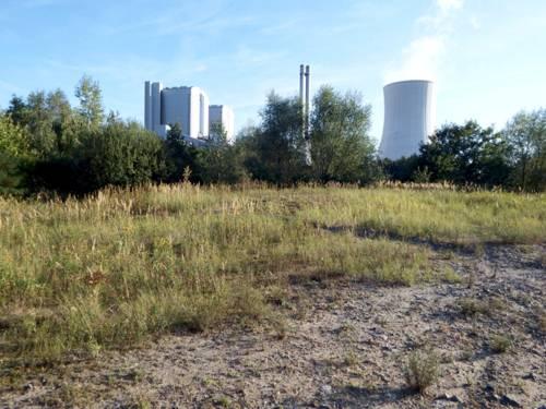 Eine Brachfläche vor einem Kraftwerk mit Kühlturm