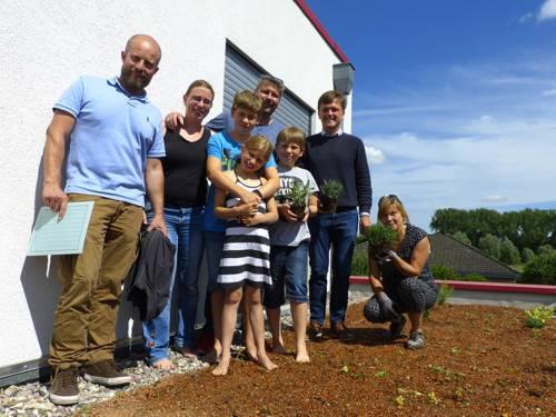 Drei Männer, zwei Frauen und drei Kinder auf einem begrünten Dach.