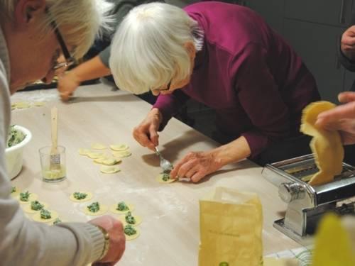 Um einen Tisch stehen Teilnehmerinnen an einem Kochkurs und stellen selber gefüllte Nudeln her.