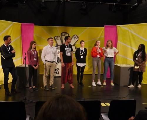Junge Menschen auf einer Bühne.