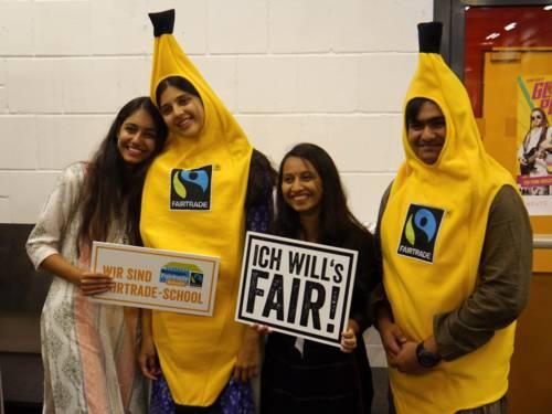 Vier junge Menschen. Zwei halten Schilder, zwei stecken in Bananen-Kostümen.