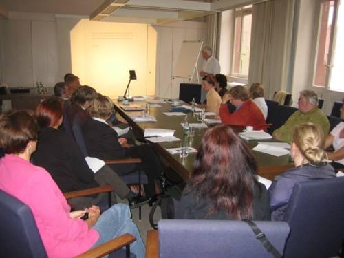 Teilnehmende der Arbeitsgruppe sitzen an einem langen Tisch und hören einen Vortrag