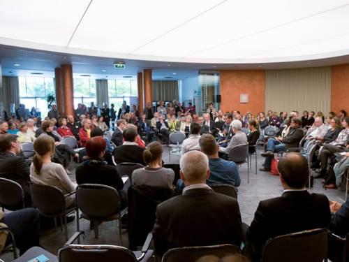 In einem großen Saal sitzen Diskutierende und Publikum