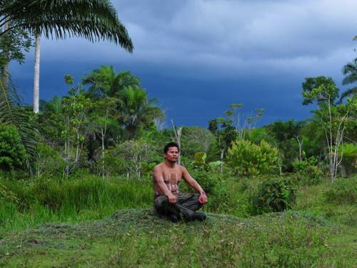 Ein Bewohner des Regenwaldes sitzt im Schneidersitz auf einer Anhöhe im kolumbianischen Amazonas-Gebiet