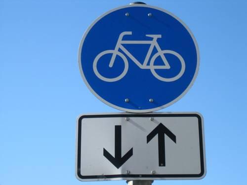 Blaues Hinweisschild mit Pfeilen für einen Fahrradweg in beide Richtungen