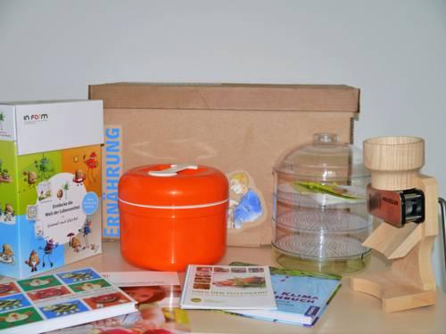 """Bücher, Broschüren, Keimgerät, Getreidemühle sind Teile des Unterrichtsangebots """"Aktivkiste Ernährung"""""""