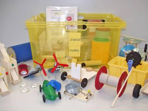 Eine gelbe Plastikkiste mit dem Aufkleber Energie und zahlreiche Miniaturmodelle zum Experimentieren