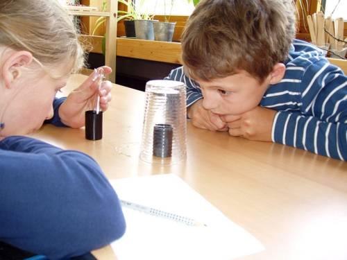Ein Mädchen und ein Junge, die an einem Tisch sitzen, untersuchen mit Hilfe eines umgestülpten Glases klimatische Veränderungen in zwei Gefäßen