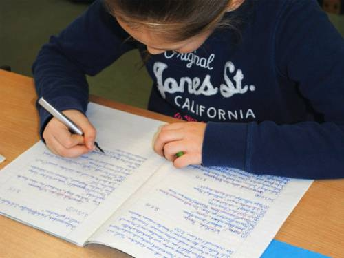 Ein Mädchen schreibt mit einem Füllfederhalter in einem Recycling-Schulheft.