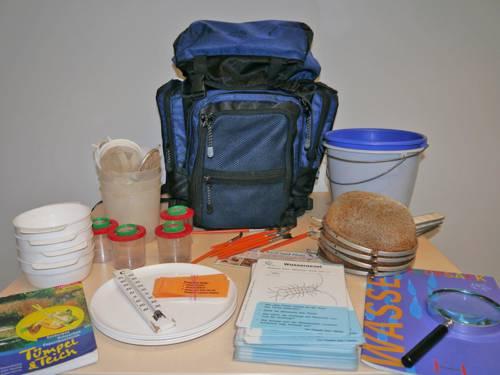 Ein blauer Rucksack steht zusammen mit vielen Utensilien, die man zur Untersuchung von Wasserproben benötigt, auf einem Tisch: Becher, Siebe, Bestimmungskarten, Eimer, Schalen, Broschüren