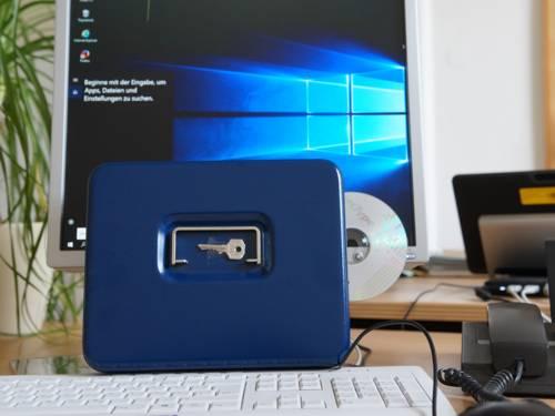 Vor einem Computer steht eine abschließbare Kassette mit einem Schlüssel.