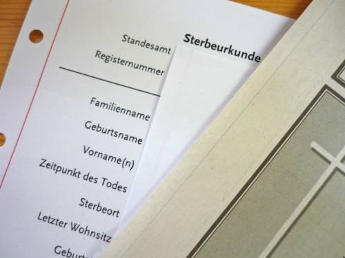 Sterbeurkunde - ein Formular, dessen Eintragungen durch ein anderes Blatt verdeckt sind.