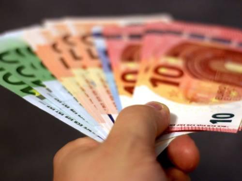 Aufgefächerte Euroscheine in einer Hand vor schwarzem Hintergrund.