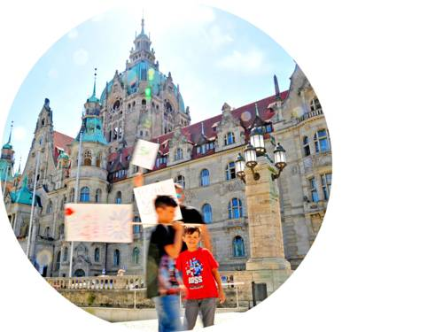 Zwei Kinder und ein Mann halten Schilder vor dem Neuen Rathaus hoch.