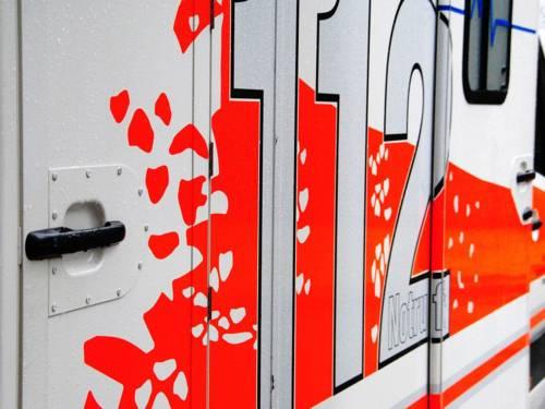 """Nahaufnahme der rechten Seite eines weißen Rettungswagen mit roten Flecken und der Aufschrift """"112""""."""