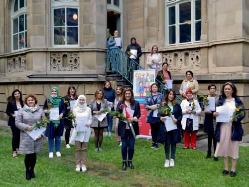 Eine Gruppe Frauen mit Blumen und Zertifikaten in den Händen posiert vor einem historischen Gebäude.