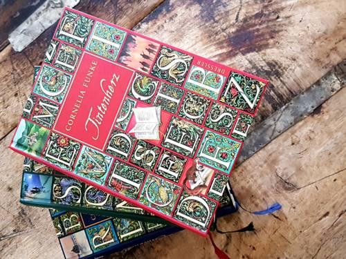 Drei bunte Bücher liegen übereinander aufgefächert auf dunklen Holzstreben.