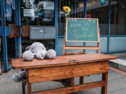 """Ein alter Schultisch, an dem ein Plüschelefant sitzt, und eine alte Schultafel, an der eine Sonnenblume festgemacht ist, mit der bunten Aufschrift """"Hurra, ich bin ein Schulkind"""""""