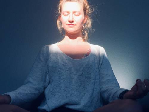 Eine meditierende Frau im Schneidersitz