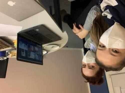 Zwei junge Frauen sitzen vor einem Laptop, auf dem ein Videochat geöffnet ist.