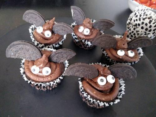 Fünf braune Muffins mit Augen und Flügeln, die an Fledermäuse erinnern.