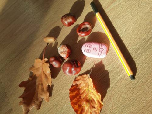 Braune Blätter, Kastanien, eine Eichel, ein Fineliner und ein Radiergummi mit Gesicht liegen auf einer Fläche.