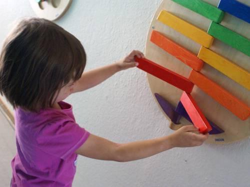 Ein Kind steht vor einer Wand, an der ein Holzspielgerät befestigt ist, mit dem das Kind hantiert.