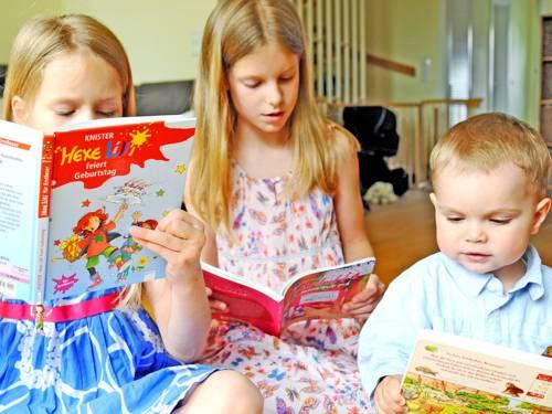 Drei Kinder hocken mit Büchern auf dem Boden.
