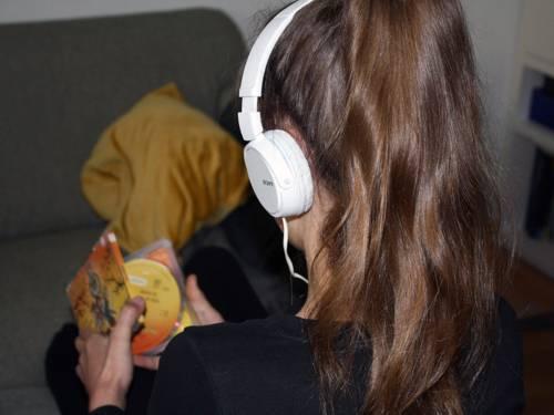 Ein Mädchen mit Kopfhörern auf dem Kopf und einer CD in der Hand ist von hinten zu sehen.