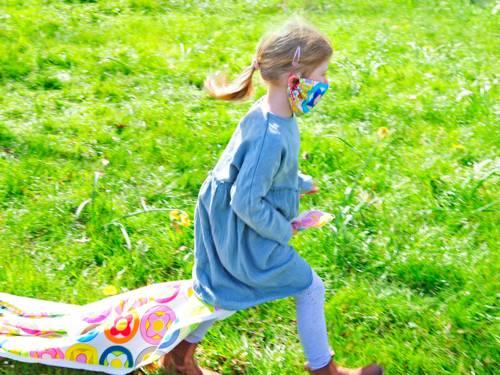 Ein Mädchen mit Mundschutz spielt auf einer Wiese.