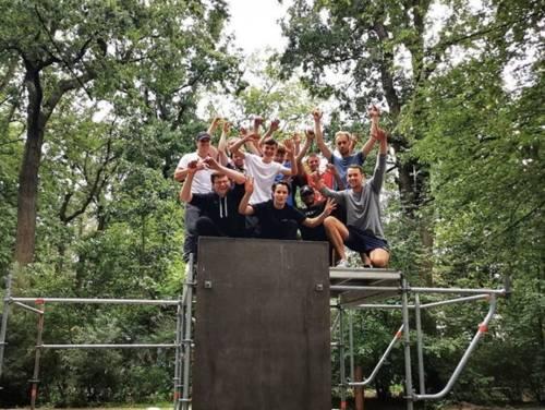 Eine Gruppe jubelnder junger Menschen auf einem Gerüst in einem Wald.
