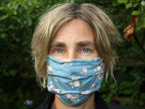 Kopf von vorne mit aufgesetztem Mund-Nasen-Schutz