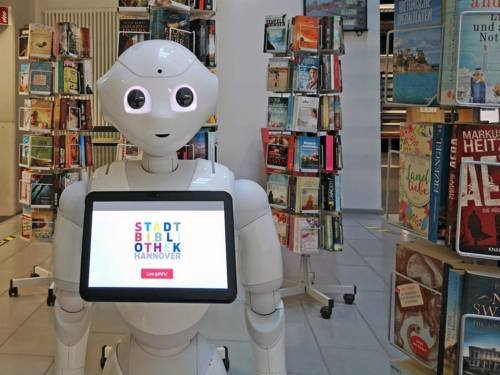 Ein Roboter steht umgeben von Bücherständern in einer Bibliothek.