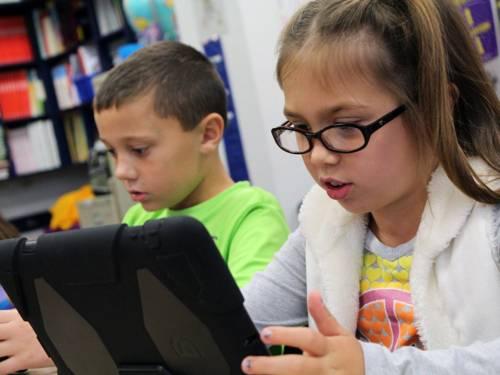Eine Schülerin und ein Schüler arbeiten an Tablets.