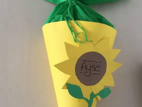 Eine gelbe Schultüte mit einer Sonnenblume und Namensschild aus Pappe.
