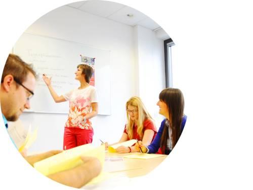 Eine Frau zeigt Erwachsenen an Tischen etwas an einem Whiteboard.