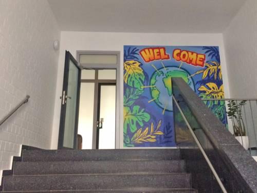 """Eine Treppe führt zu einer offenen Tür, neben der eine bunte """"Welcome""""-Zeichnung hängt."""